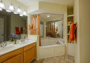 Bathroom with two-sink vanity and garden tub in a two-bedroom presidential villa at the Holiday Hills Resort in Branson Missouri.