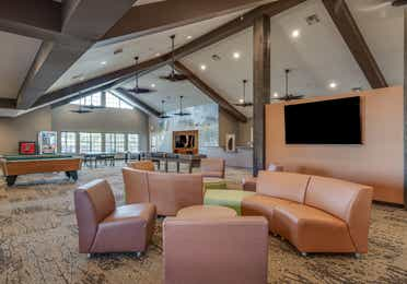 Game room with comfortable seating, a flat screen TV, pool tables, and ping pong tables at Piney Shores Resort in Conroe, Texas