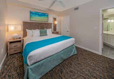 Bedroom with attached bathroom and coastal decor in a one-bedroom villa at Panama City Beach Resort