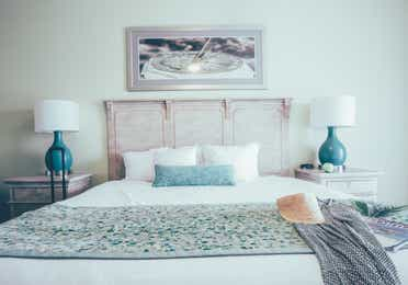 Bedroom with coastal decor and two night stands in a villa in River Island at Orange Lake Resort near Orlando, Florida