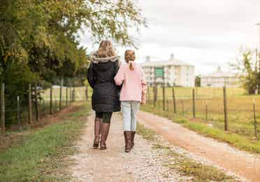Mother and daughter walking down a dirt path towards a resort hotel.