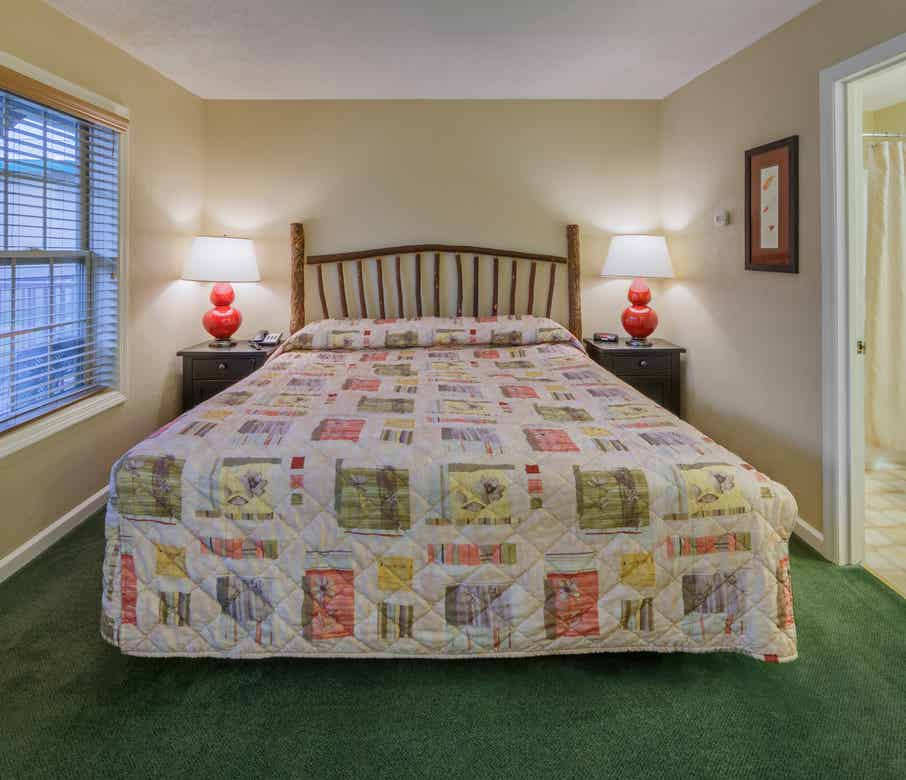 King bed in a bedroom of a three bedroom villa at Oak n' Spruce Resort in South Lee, Massachusetts