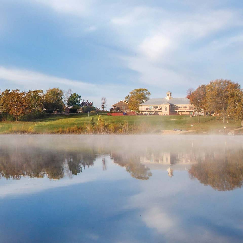 Lake with fog rolling on top and view of Timber Creek Resort property building and trees in De Soto, Missouri.