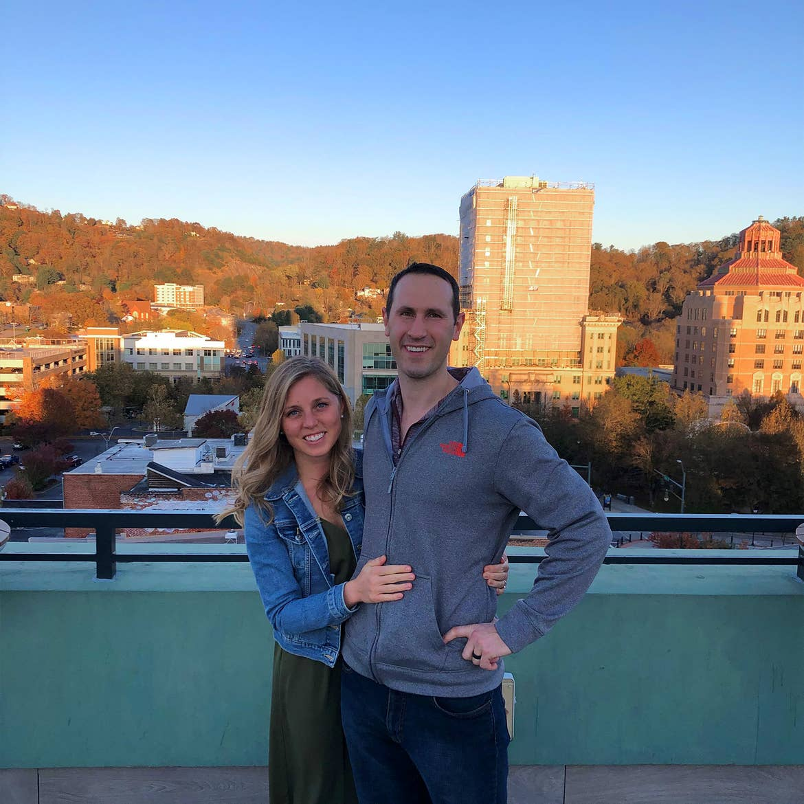 A blonde woman (left) wearing a denim jacket and green maxi dress hugs a man (right) wearing a grey zip-up hoodie on a rooftop bar overlooking the downtown area of Asheville, North Carolina.