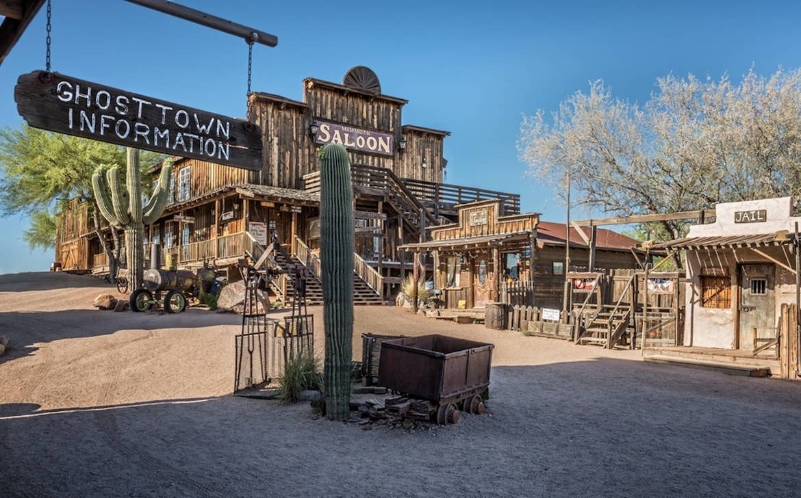 A view of a cactus and miscellaneous old-western items with a saloon and shops in the background in Goldfield, Arizona.