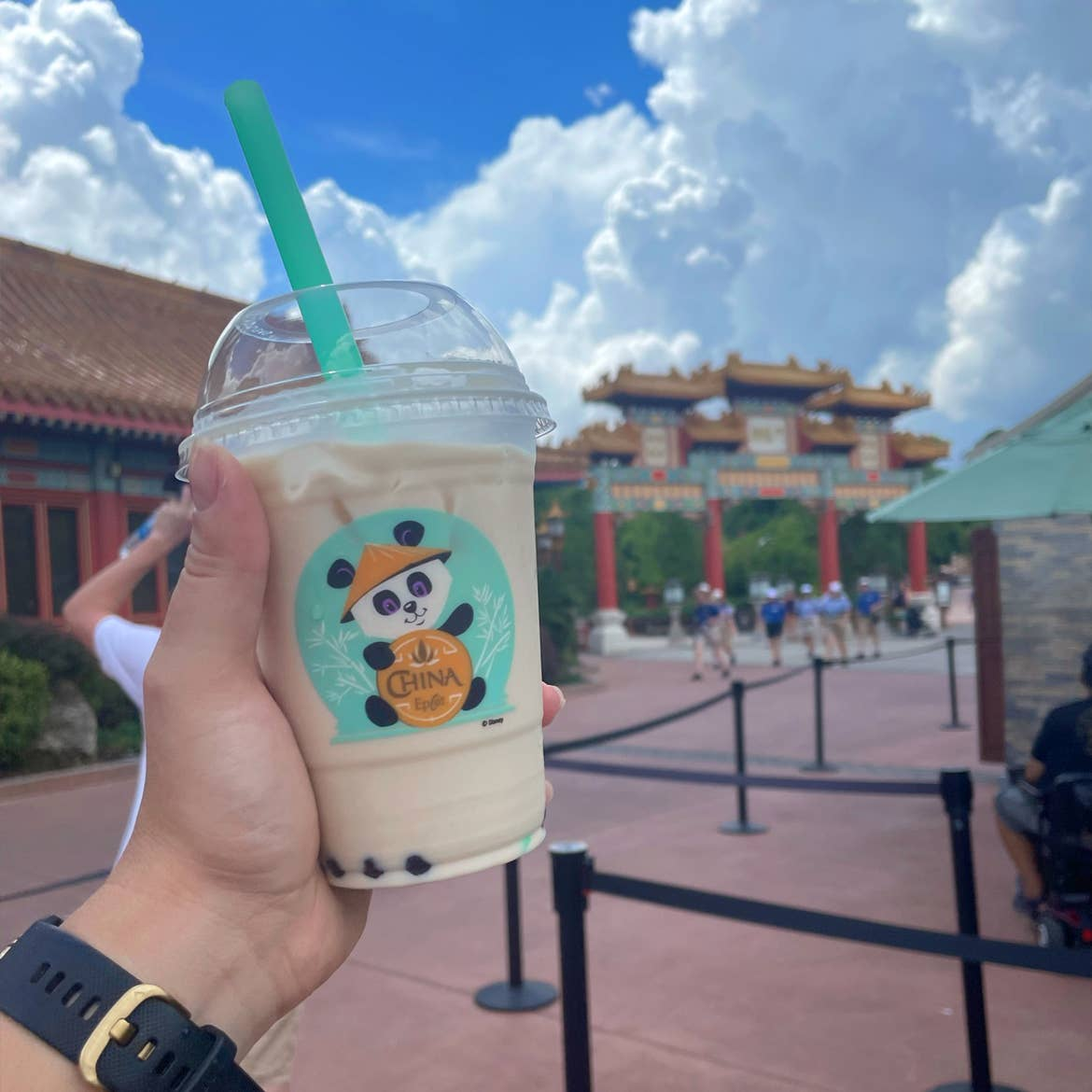 A hand holds a plastic cup of bubble tea with a panda graphic near the China Pavilion at Epcot.