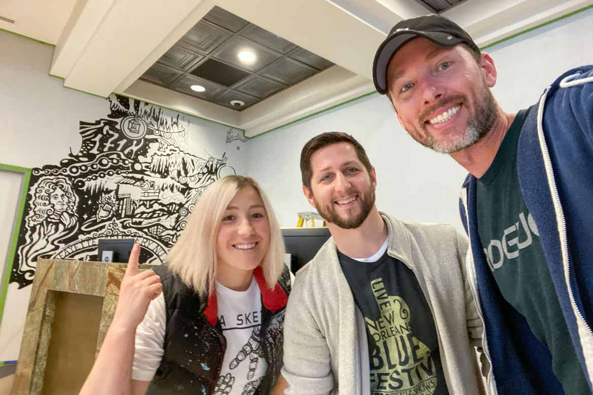Co-authors, Ben Henderson (right) and Andrew Burns (middle) stand with Mila Sketch in front of her mural at our resort in New Orleans, Louisiana.