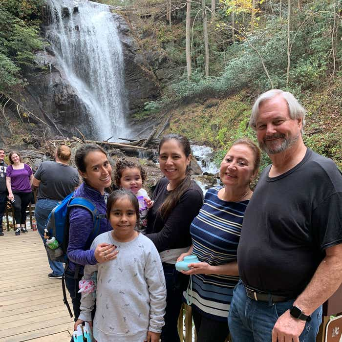 Featured author, Andrea Beltran (left), poses near a waterfall wearing a blue hiking backpack and purple pull-up sweater with her family.