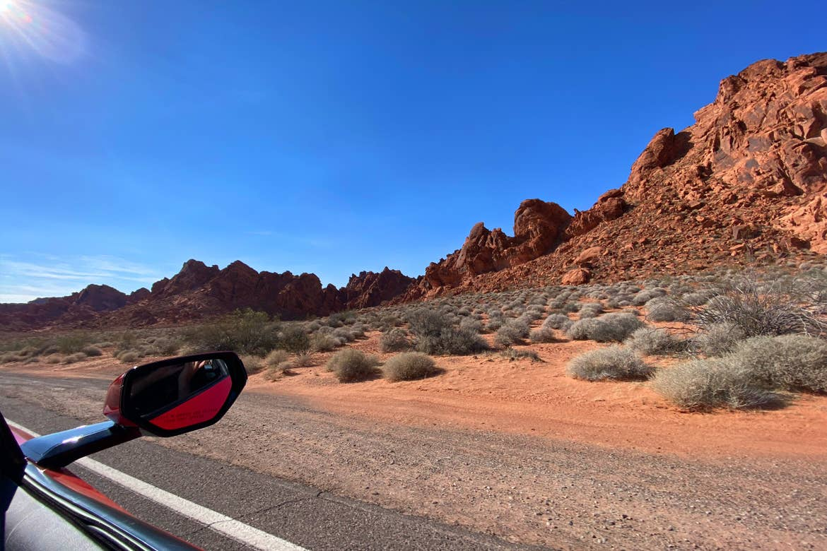 A car mirror from the passenger side encroaches the Valley of Fire rock formations while driving down a black asphalt road.