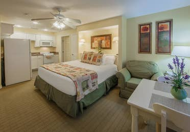Bed with kitchen and dining area in a two-bedroom presidential villa at the Hill Country Resort in Canyon Lake, Texas.