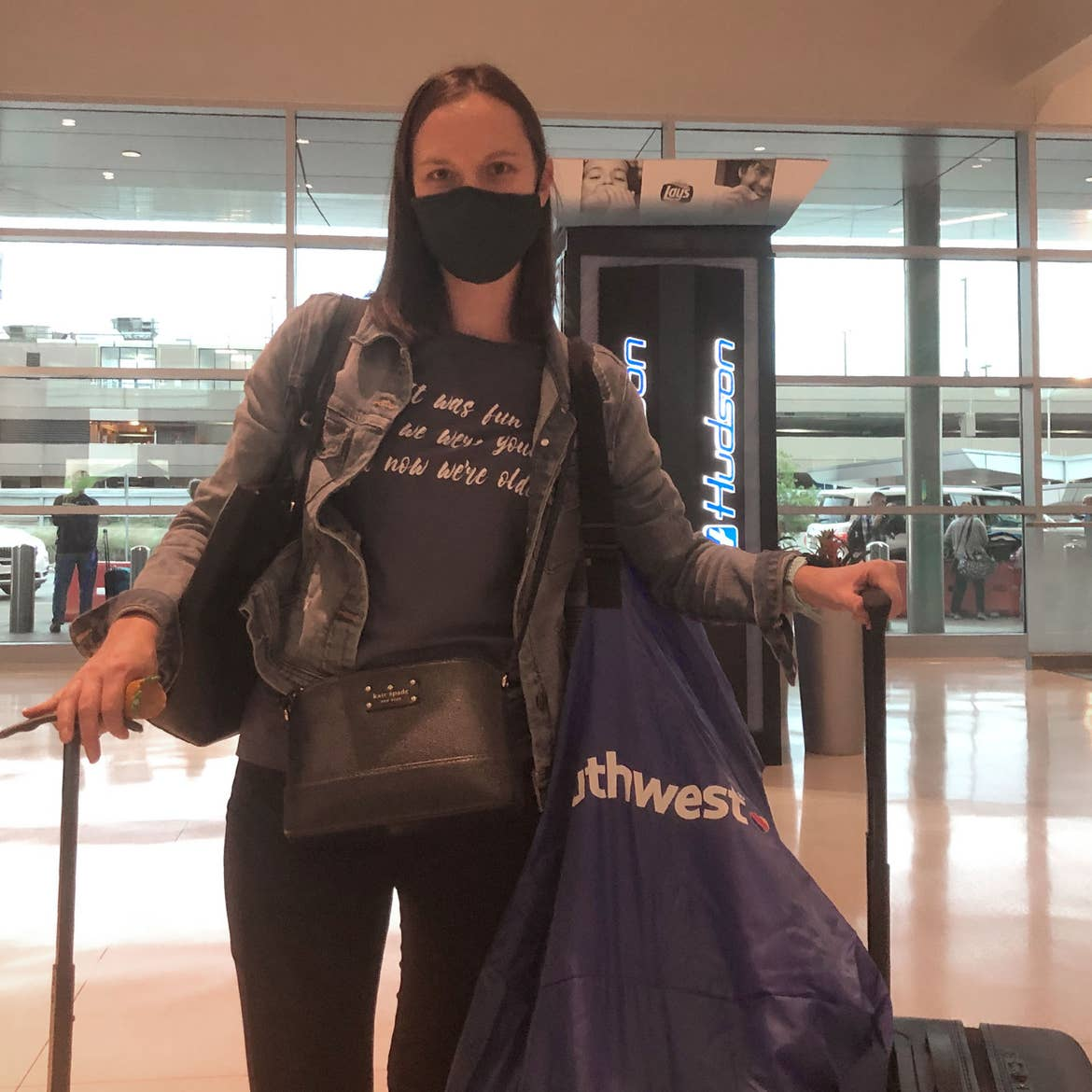 Author, Sarah, stands wearing a mask and holding several bags and suitcases containing the necessities for a safe flight.