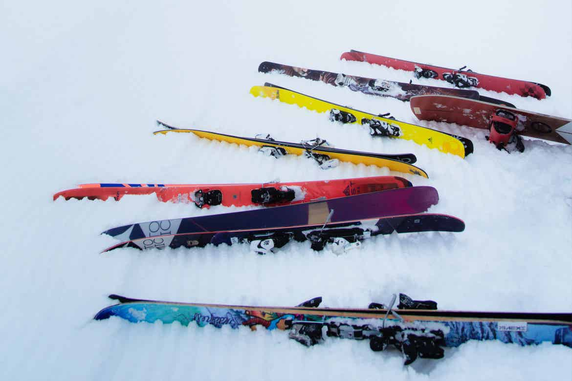 Several sets of skis sit in the snow.
