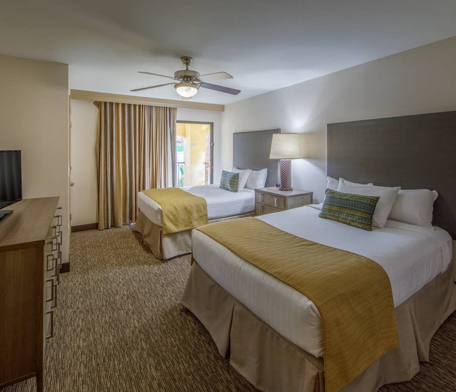 Guest bedroom with two double beds and a flat screen TV in a two-bedroom villa at Scottsdale Resort