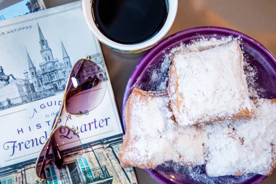 A tabletop with three beignets on a purple plate surrounded by a pair of sunglasses, a cup of chicory coffee in a white mug, and a book with the title, 'A Guide to the Historic French Quarter.'