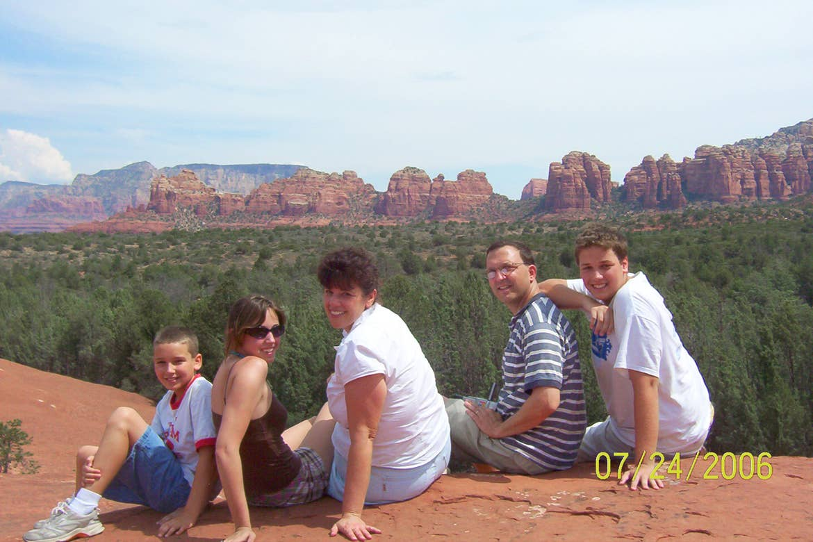 A caucasian family sits facing the camera in front of Sedona Red rocks.