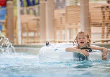 Young girl floating on an inter-tube in lazy river