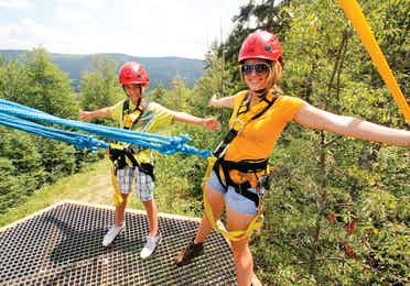Two women ready to zipline through the forest