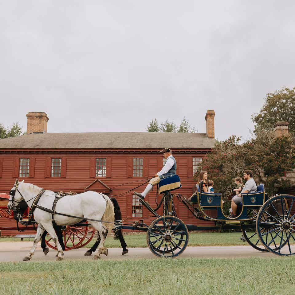 Family taking ride on horse-drawn carriage in Williamsburg, Virginia near Williamsburg Resort.