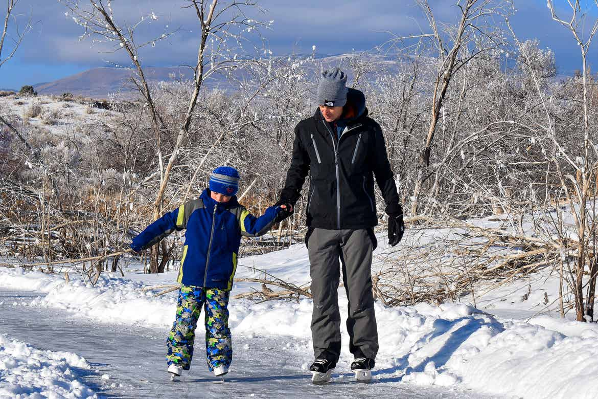 Featured Contributor, Jessica Averett's husband (right) wears a black winter coat, snow pants, and white ice skates as he helps his son (right) wearing blue and lime winter jacket, snow pants, and white ice skates outside.