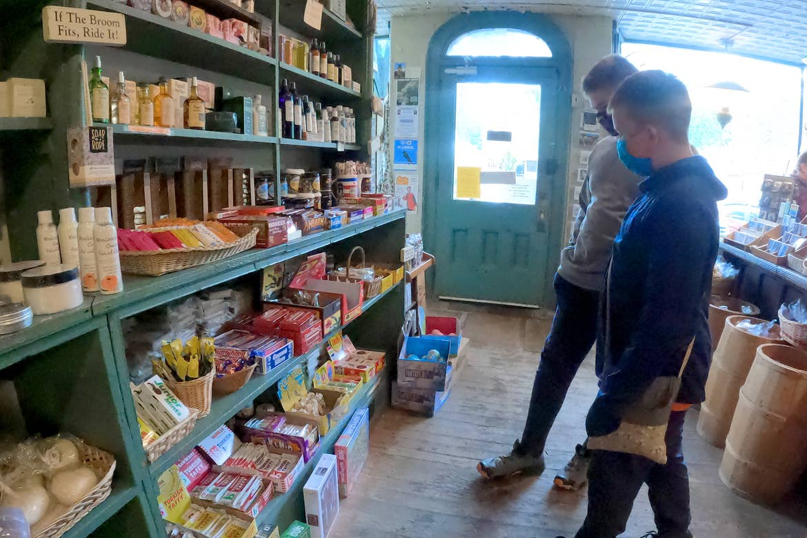 Two caucasian tween boys wearing long pants, hoodies and safety masks stand inside a candy store looking at various treats on the wall.
