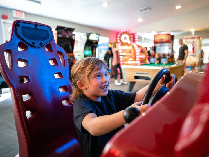 Young child playing arcade racing game at Desert Club Resort in Las Vegas, Nevada.