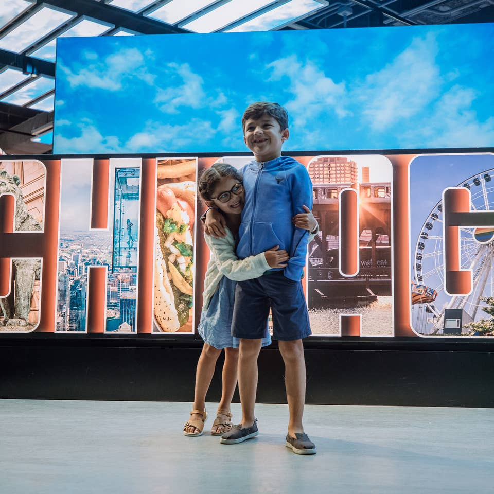 Kids hugging n front of Chicago sign at Chicago, Illinois.