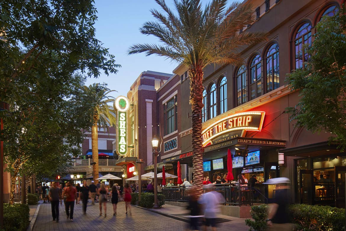 Several people walk near building exteriors of restaurants and shops on Las Vegas Fremont Street.