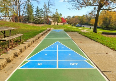 Outdoor shuffleboard court and nearby picnic tables at Fox River Resort in Sheridan, Illinois