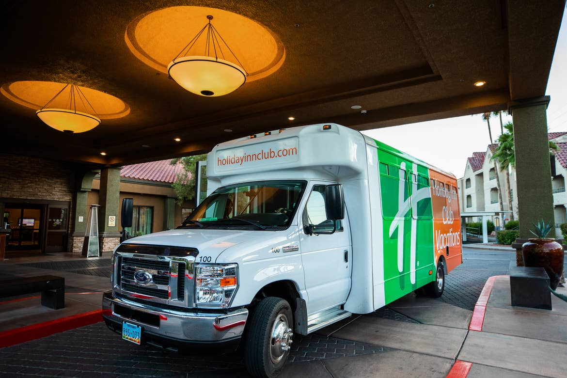 A white shuttle bus with an orange and green decal that reads, 'Holiday Inn Club Vacations' sits under the vestibule of the Desert Club Resort entrance.