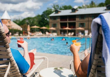 Two guests having drinks from the Tiki Bar by the pool at Oak n' Spruce Resort in South Lee, Massachusetts.