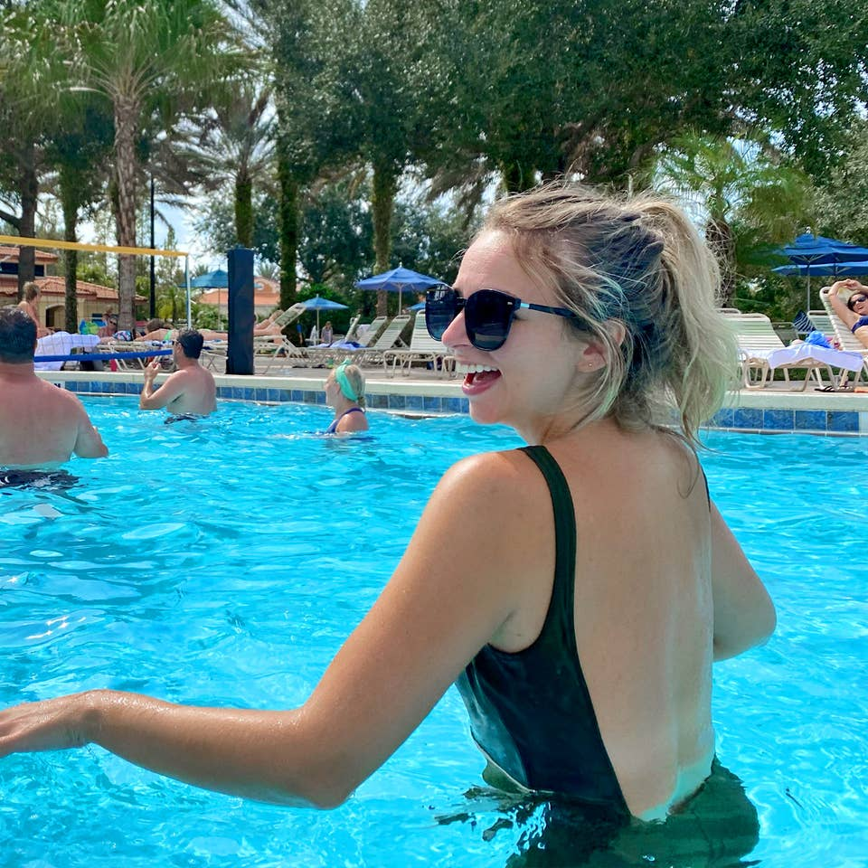 Featured Contributor, Angie Orth, wears a black swimsuit in the pool at our Orange Lake Resort in Orlando, Florida.