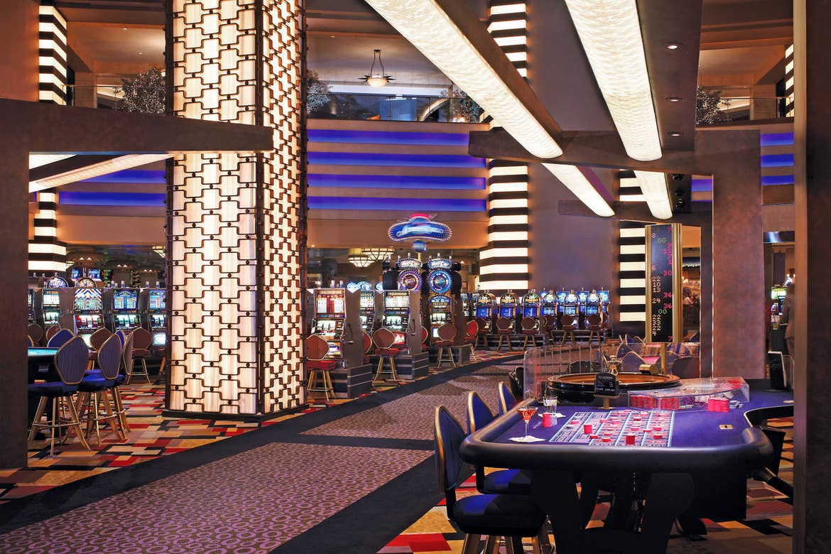 The interior of the Planet Hollywood casino floor with various lighting, digital slot machines and playing tables.