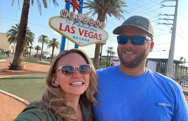 A caucasian woman wearing sunglasses (left) poses near a caucasian man wearing sunglasses and a hat (right) in front of the 'Welcome to Las Vegas Nevada' marquee sign.
