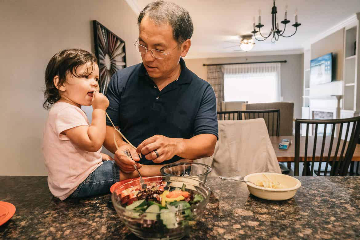 Featured Contributor, Angelica Kajiwara's husband (right), and their daughter prep food in the villa kitchen of our Williamsburg resort in Williamsburg, Virginia.