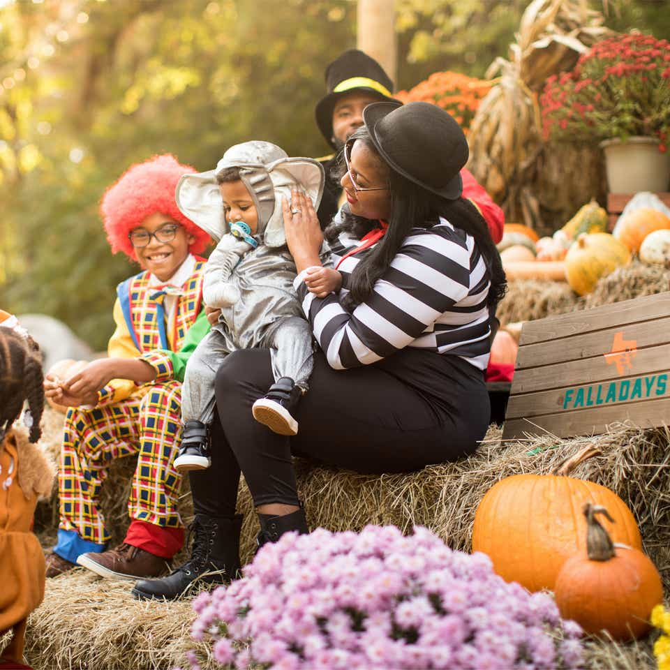 Family in costumes sitting on a pumpkin patch at the Villages Resort in Flint, TX