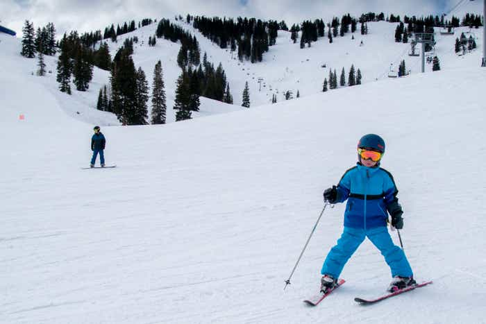 Jessica's son clad in winter and skiing gear ascends from the trail.