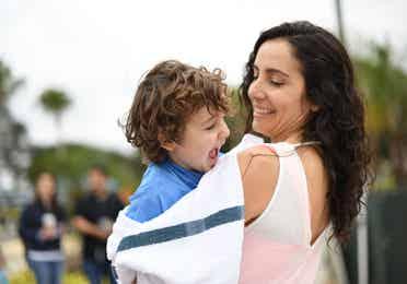Mom and holding young boy by pool at Orange Lake Resort near Orlando, Florida