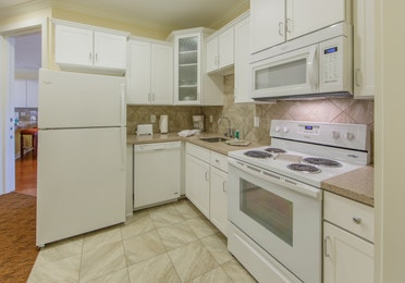 Kitchen with fridge, oven, microwave, sink, and dishwasher in a presidential villa at Fox River Resort in Sheridan, Illinois