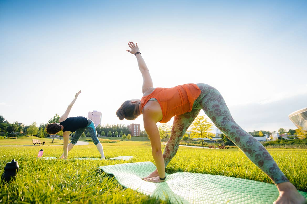 Two women doing Yoga poses on a green lawn outdoors.