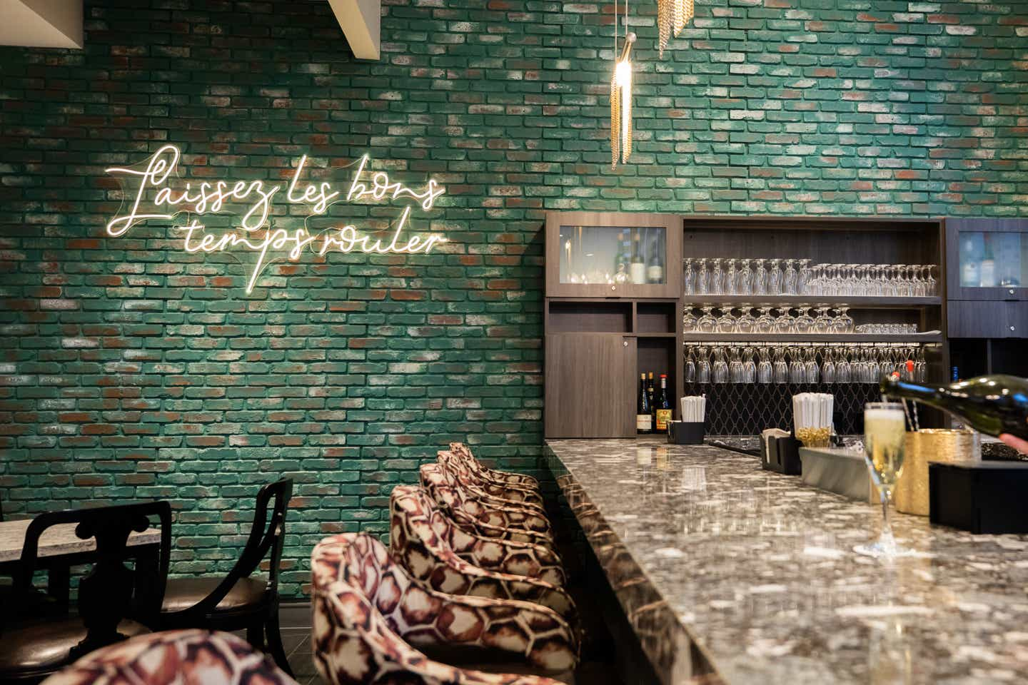 A green brick wall with a neon sign that reads, 'Laissez les bons temps rouler' featured in the Maritime Bar & Lounge at our resort in New Orleans, Louisiana.