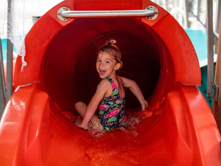 Small child preparing to go down waterslide at The Waterpark at The Villages at Villages Resort in Flint, Texas.