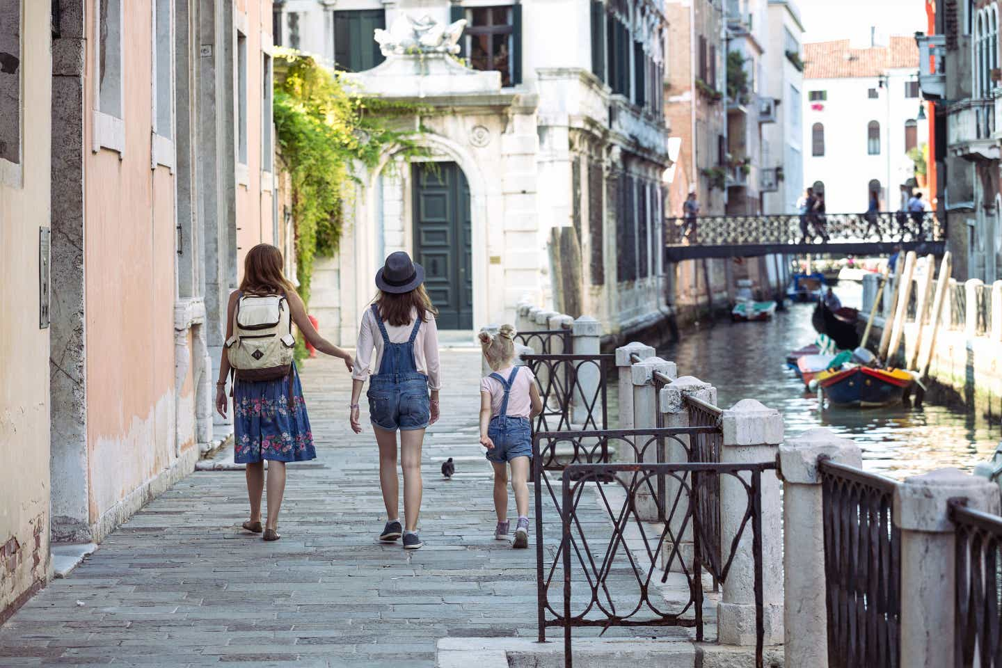 A woman (left) and her two daughters (middle and far-right) walk along the riverwalk of Venice, Italy.