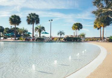 Zero-entry pool surrounded by palm trees in West Village at Orange Lake Resort near Orlando, Florida