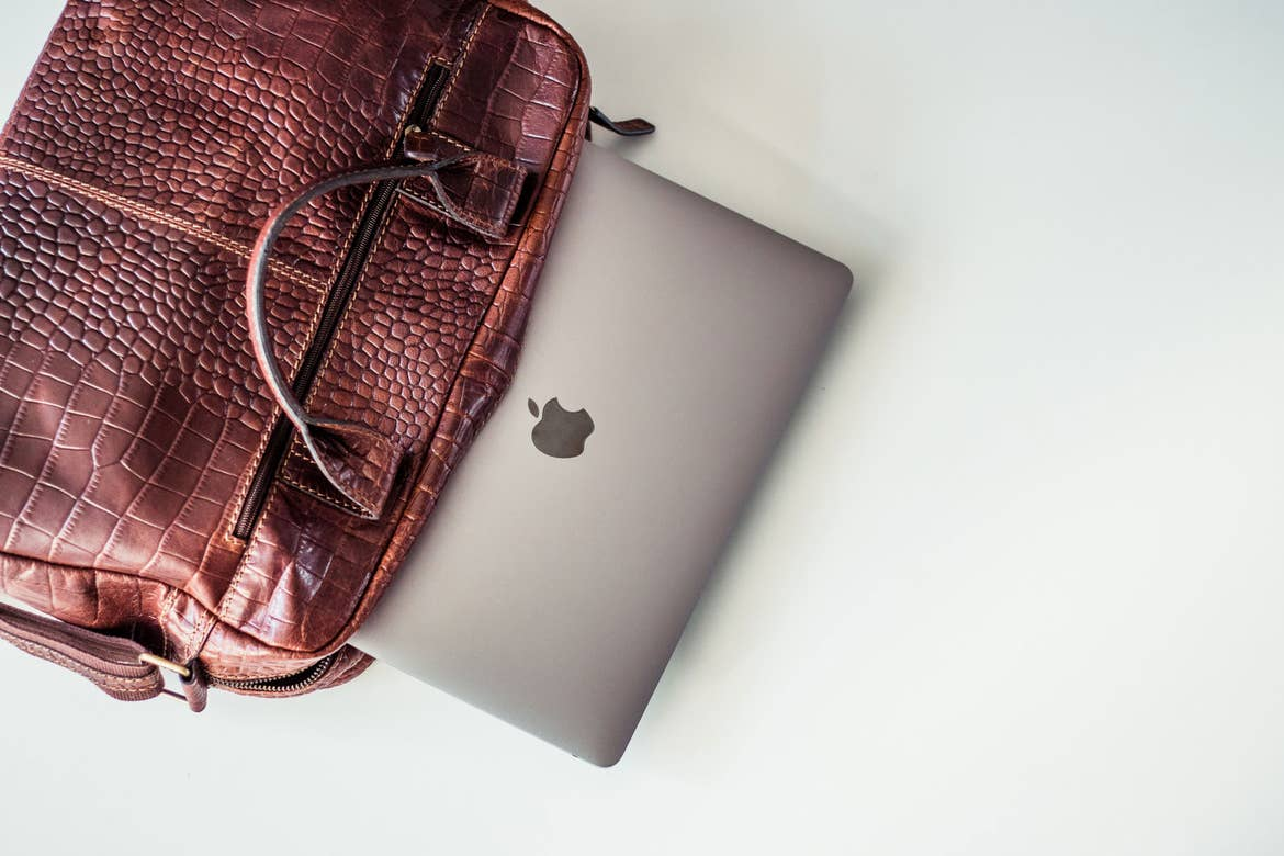 Laptop being removed from work bag over a white table.