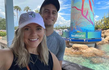A Caucasian female wearing a pink baseball cap and black tank top stands near the lighthouse in SeaWorld Orlando.