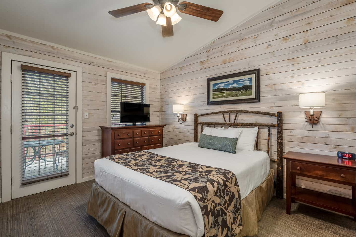 Bedroom with flat screen TV and ceiling fan in a two bedroom cabin at Piney Shores Resort in Conroe, Texas