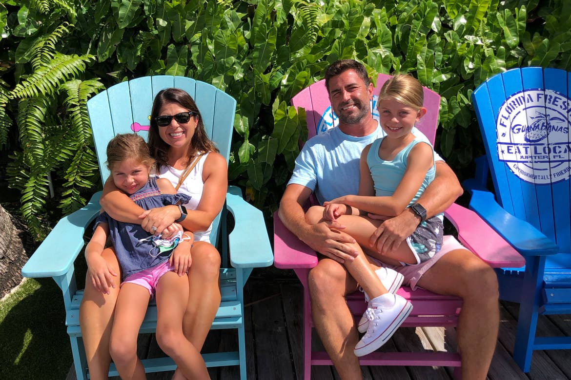 Featured Contributor, Chris Johnston (middle-left), sits with her husband, Josh (middle-right), and two daughters, Kyler (front-left) and Kyndall (front-right), on brightly colored Adirondack chairs.