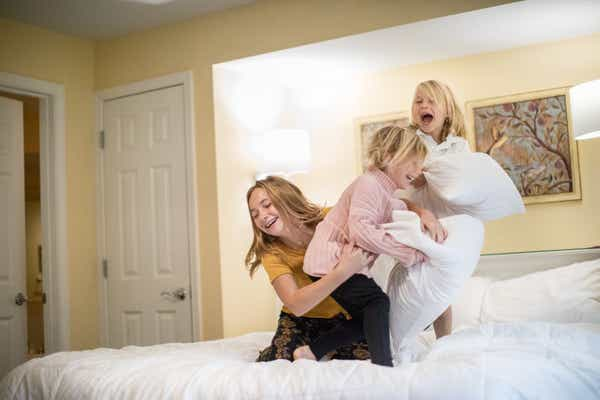Three children laughing and having a pillow fight on a bed.