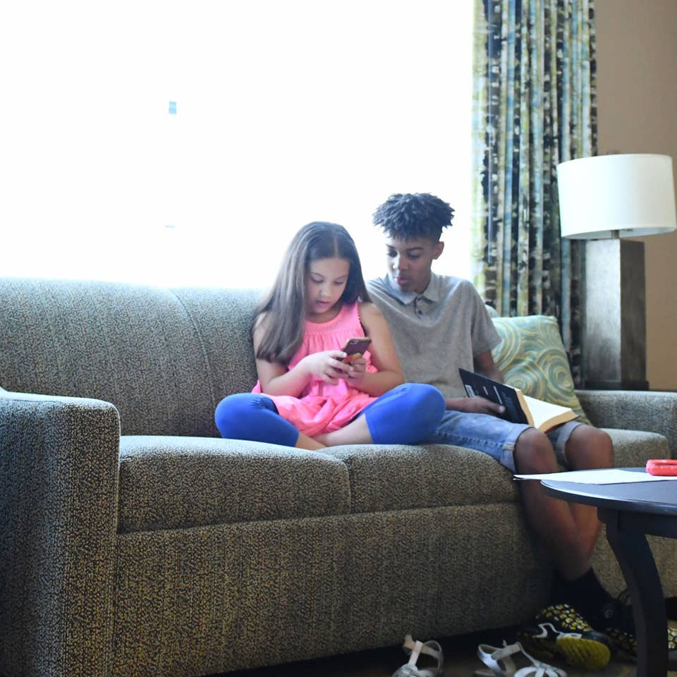 Two children sitting in a living room in a villa looking at smartphone together