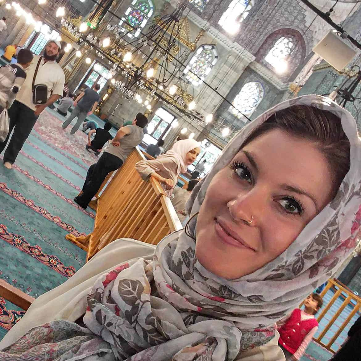 Featured Contributor, Ashlyn George, wears a culturally-appropriate headscarf at a mosque in Istanbul.